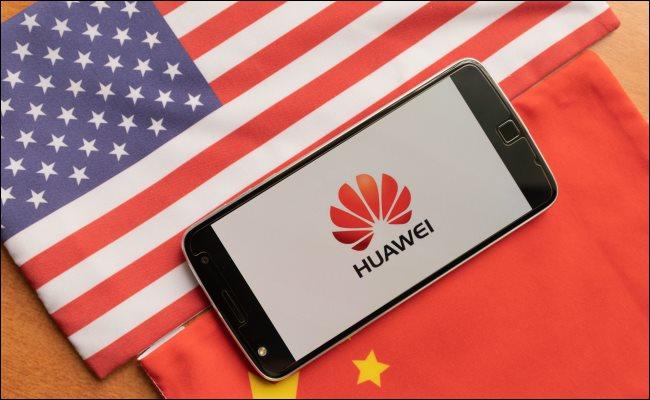 Un téléphone Huawei entre un drapeau américain et chinois.