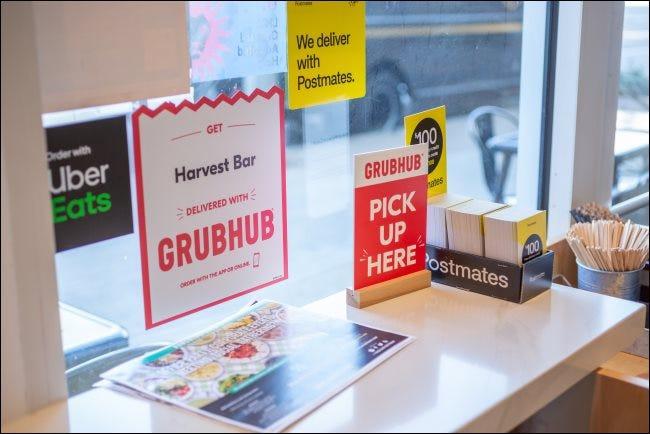 Signes pour GrubHub, Postmates et Uber Eats dans un restaurant.