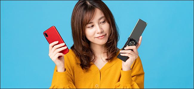 Une femme tient un téléphone à clapet et un iPhone.  Elle regarde vers le téléphone à clapet - vers une époque révolue depuis longtemps ...