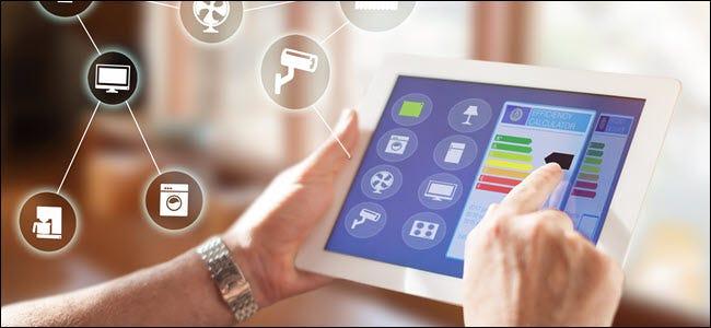 Les mains d'un homme à l'aide d'une tablette pour contrôler les appareils intelligents dans une application.
