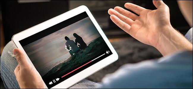 """Les mains d'un homme tenant une tablette affichant un """"Chargement en cours"""" icône sur une vidéo."""