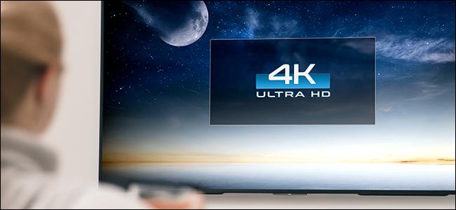 Personne regardant une télévision grand écran 4K.