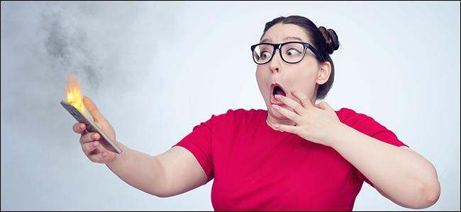 Une fille panique tout en tenant un téléphone qui explose.  De toute évidence, elle n'a pas utilisé de chargeur sans fil certifié Qi.