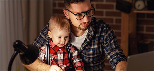 Un père et un enfant lisant quelque chose sur un ordinateur portable