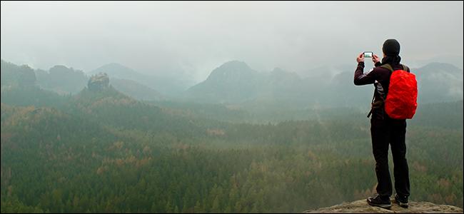 Un homme prend une photo d'une chaîne de montagnes brumeuse et dramatique.